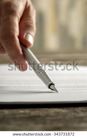 Closeup of male hand holding ink pen and pointing with it to the bottom of contract or document to the line where the signature belongs.