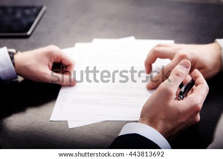 Closeup of male hand pointing where to sign a contract, legal papers or application form. - stock photo