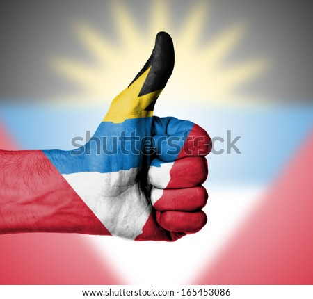 Closeup of male hand showing thumbs up sign, flag of Antigua and Barbuda - stock photo