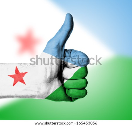 Closeup of male hand showing thumbs up sign, flag of Djibouti - stock photo