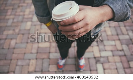 Closeup of male hand with coffee cup on street food festival - stock photo