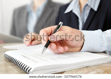 Closeup of Male Hand with Pen at the Meeting - stock photo