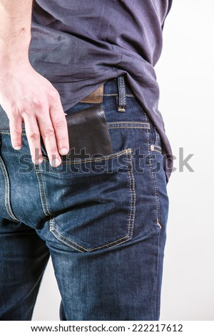 Closeup of male hands. Careless man taking the wallet out on his back pocket. Risk of theft. Isolated on white. Studio shot. - stock photo