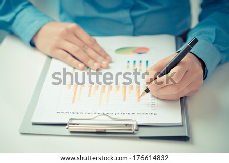 Closeup of male hands holding a ballpoint and analyzing the financial data on the foreground  - stock photo