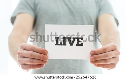 Closeup of male hands holding a meaningful sign with the word Live in a conceptual image. - stock photo