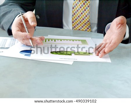 Closeup of male hands holding pen over financial  charts