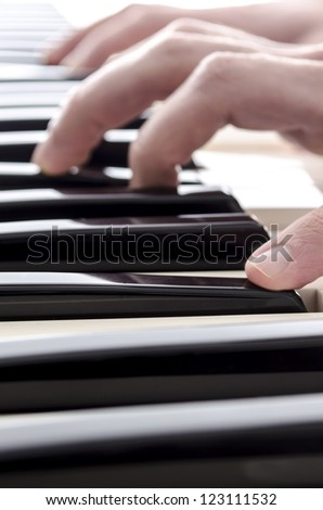 Closeup of male hands playing digital piano.