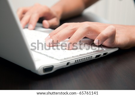 Closeup of male hands typing on a laptop in the office - stock photo