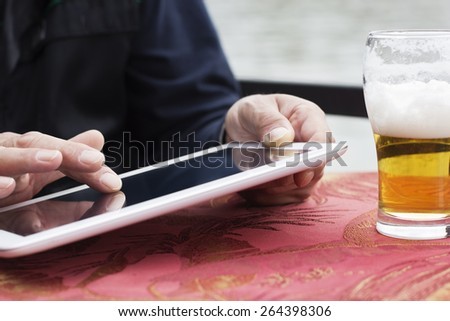 Closeup of male hands with with digital tablet surfing the net .The man sitting at the table in the pub  outdoors and drinking a beer.  - stock photo