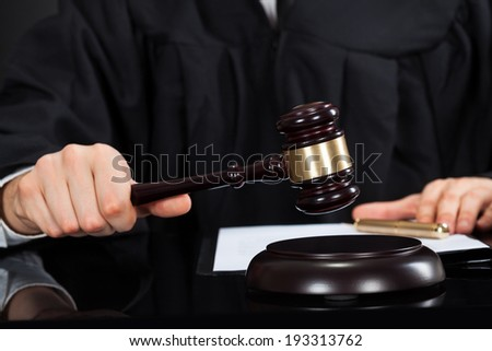 Closeup of male judge with mallet at desk - stock photo