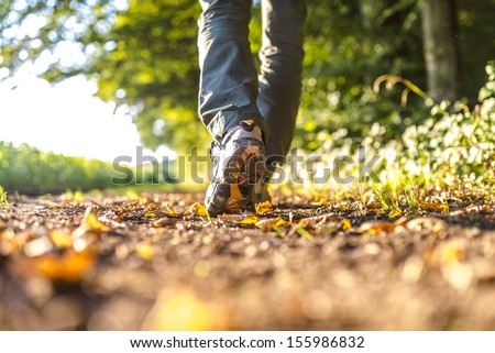 Closeup of male legs hiking in nature. - stock photo