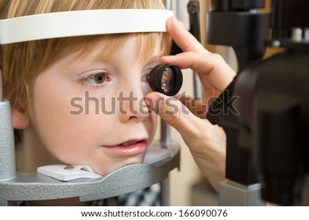 Closeup of male optician's hand examining boy's retina with lens in clinic - stock photo