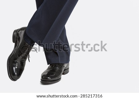 Closeup of Male's Stylish Oxfrod Brogue Shoes Posing with Legs Crossed. Horizontal Image - stock photo