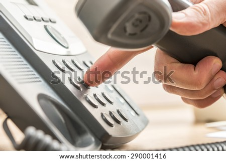 Closeup of male telemarketing salesperson holding a telephone receiver dialing phone number to make a business call. - stock photo