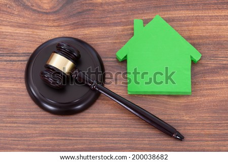 Closeup of mallet on block by green house model in courthouse - stock photo
