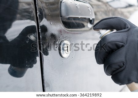 Closeup of man hand with lock door de-icer