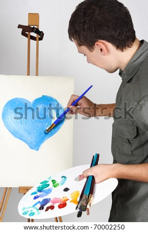 closeup of man holding brushes and palette, painting blue heart