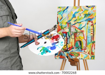 closeup of man holding brushes and palette, painting picture with abstract city - stock photo