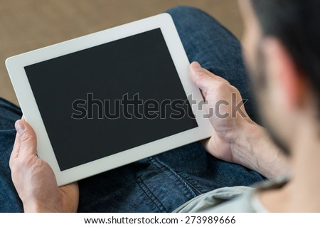 Closeup of man holding digital tablet sitting on sofa