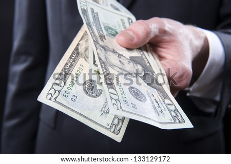 Closeup of man in suit offering cash - stock photo