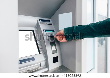 Closeup of man inserting credit card in ATM machine - stock photo