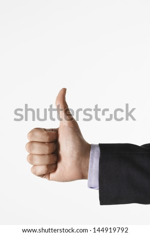 Closeup of man making thumbs up sign against white background - stock photo