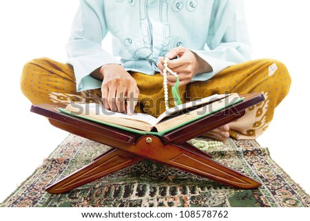 Closeup of man reading quran and pointing at the quran - stock photo