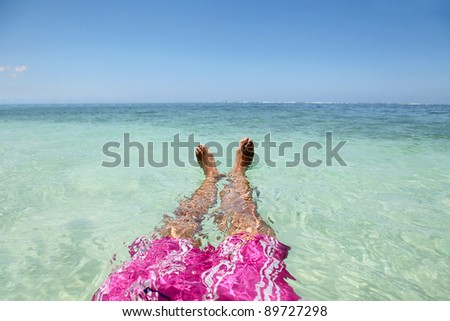 Closeup of man's feet floating in blue lagoon water - stock photo