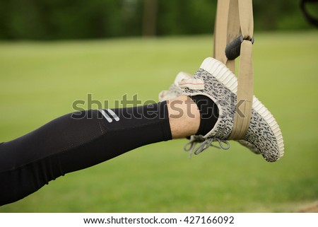 Closeup of man's feet while training before or after jogging long distance. Man's feet in jogging shoes in green park or forest. - stock photo