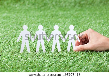Closeup of man's hand holding paper people chain on grass - stock photo