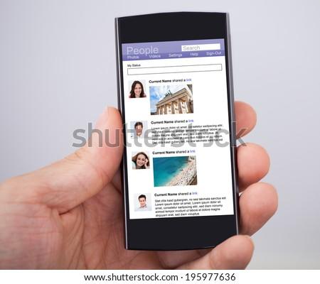 Closeup of man's hand holding smartphone with social site displayed on screen - stock photo