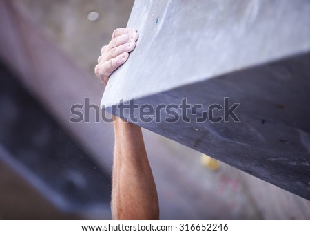 Closeup of man's hand on handhold on artificial climbing wall, hand in focus - stock photo