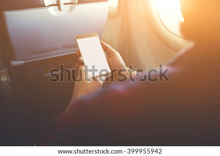 Closeup of man`s hands is holding mobile phone with empty copy space screen for your advertising text message or content.Hipster guy is reading electronic book on cell telephone during flying in plane - stock photo