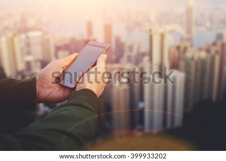 Closeup of man`s hands is holding smart phone with copy space screen for your advertising text message. Closely of male manager is watching wold news online via cell telephone during work break - stock photo
