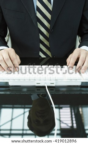 Closeup of man's hands typing on keyboard.