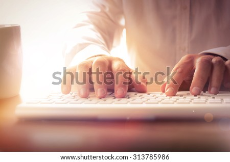 Closeup of man's hands typing on keyboard. Image can be used for background, website banner, promotional materials, poster, presentation templates, advertising and printed materials. - stock photo