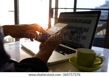 Closeup of man's hands using smartphone in moring light. - stock photo
