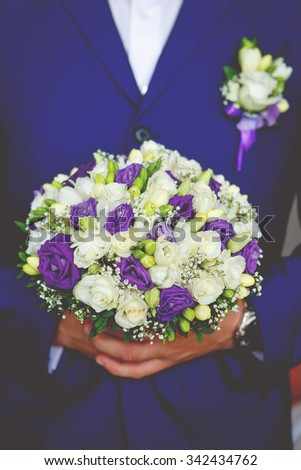 Closeup of Man the groom in the wedding blue suit with bridal bouquet with white and purple roses, flowers boutonniere on his lapel. Instagram colors toning - stock photo