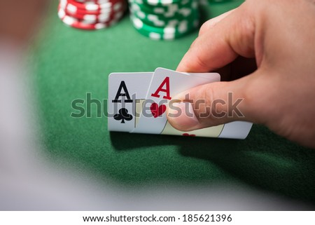Closeup of man with two aces in casino