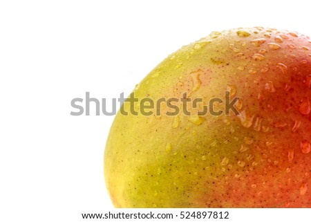 Closeup of mango red and yellow skin spotted with water droplets off centre