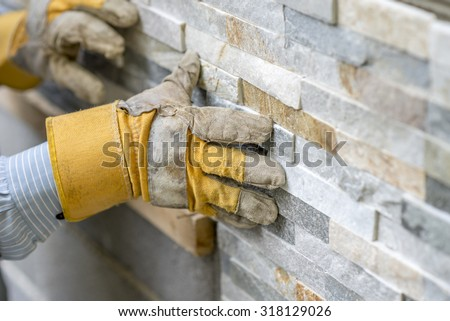 Closeup of manual worker in protection gloves pushing the tile into the cement on the wall while tiling a wall with ornamental tiles l in a DIY, renovation or construction concept. - stock photo