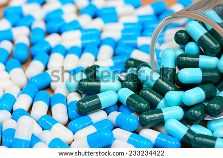 closeup of many green  and blue white  capsules   for health care concept  ; selective focus with blur foreground and background