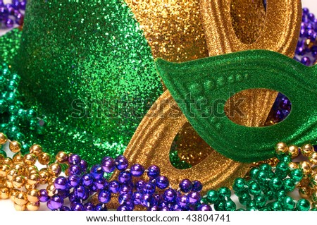 Closeup of Mardi Gras masks, hat, and beads. - stock photo