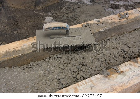 Closeup of mason's trowel on concrete shuttering blocks filled with mortar - stock photo