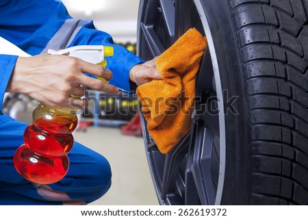 Closeup of mechanic hands giving a care on a tire rim by cleaning the dust with cloth - stock photo