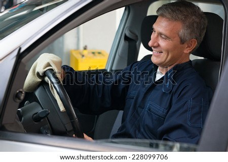 Closeup Of Mechanic Sitting On Driving Seat Cleaning Steering Wheel - stock photo