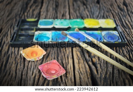 Closeup of messy, used water color paint box and paint brush - stock photo