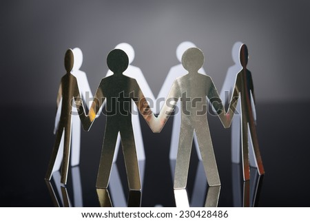 Closeup of metal team representing unity isolated over black background - stock photo