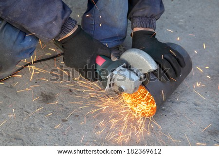 Closeup of metal tube grinding with grinder tool - stock photo