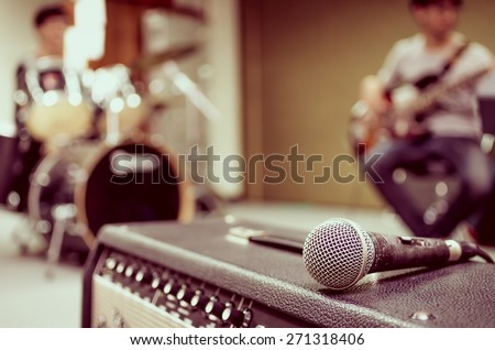 Closeup of microphone on musician blurred background - stock photo